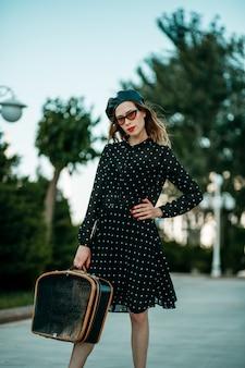 Jovem mulher em um vestido de bolinhas preto vintage com mala retrô na mão posando do lado de fora