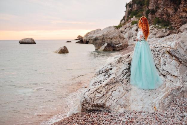 Jovem mulher em um vestido de luxo fica na costa do mar adriático