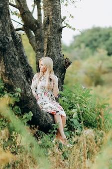 Jovem mulher em um vestido floral, sentado em uma árvore
