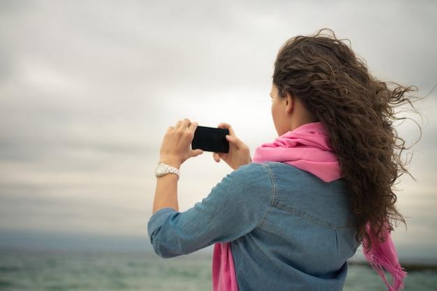 Jovem mulher em um vestido jeans com um lenço rosa tira uma foto do mar