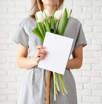 Jovem mulher em um vestido listrado segurando flores tulipa branca e um cartão em branco.