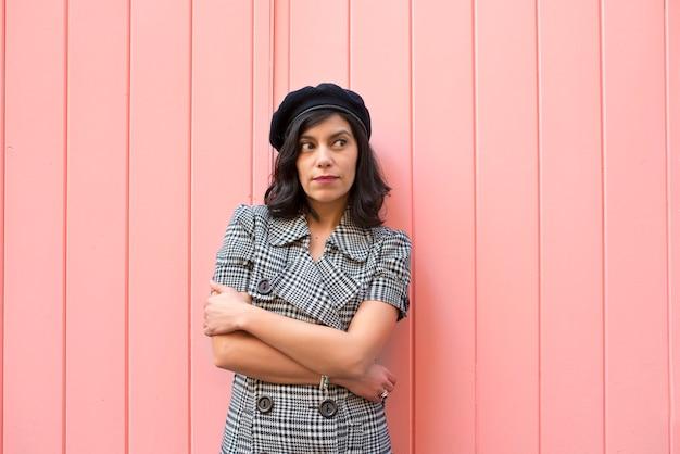 Jovem mulher em um vestido xadrez preto e branco, olhando para a direita em uma parede rosa.
