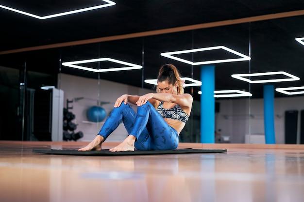 Jovem mulher em uma academia, fazendo exercícios com roupas esportivas azuis, fazendo exercícios de alongamento.