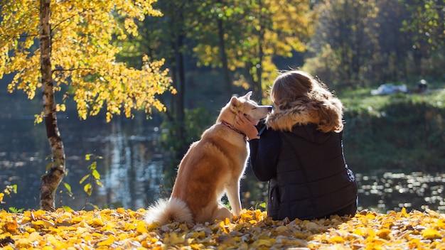 Jovem mulher em uma caminhada com seu cão raça akita inu