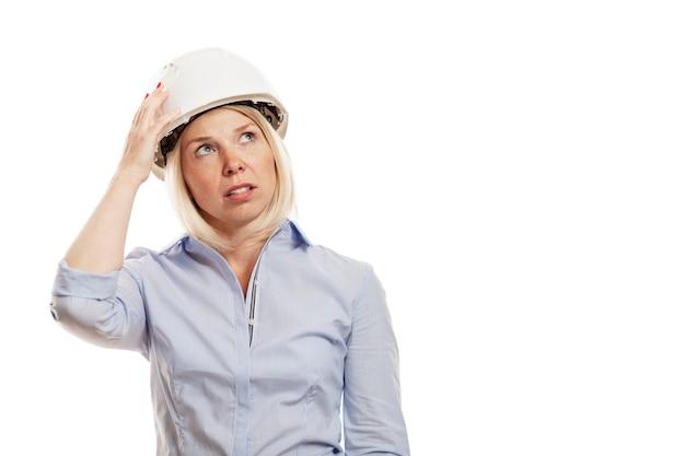 Jovem mulher em uma camisa azul e capacete branco da construção. isolado sobre a parede branca. fechar-se.