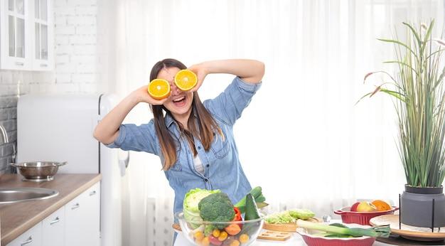 Jovem mulher em uma cozinha brilhante, posando com laranjas durante o cozimento.
