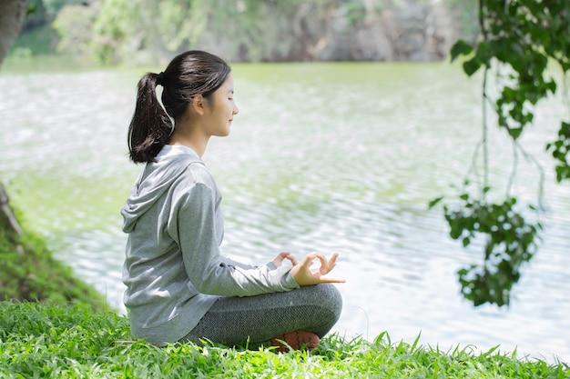 Jovem mulher em uma esteira de ioga para relaxar no parque. relaxe na natureza