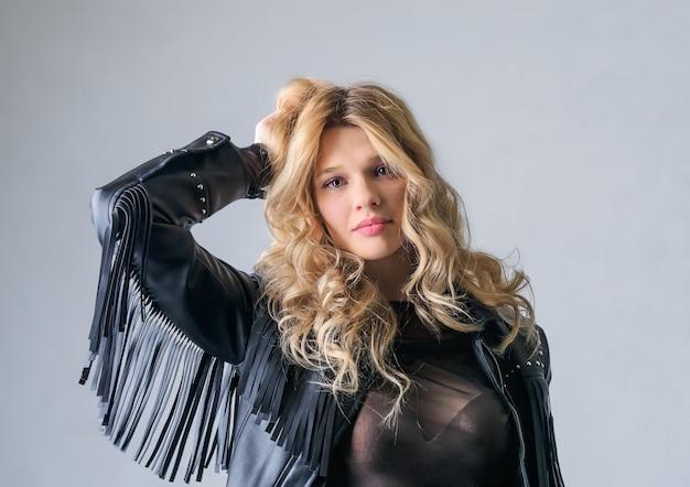 Jovem mulher em uma jaqueta de balancim de couro preto.