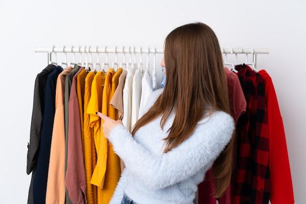 Jovem mulher em uma loja de roupas, apontando para trás com o dedo indicador