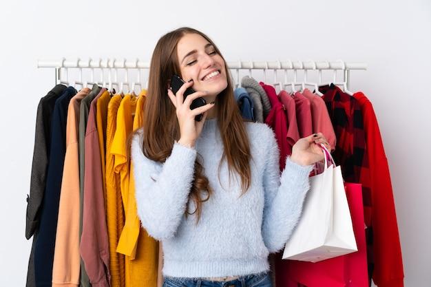 Jovem mulher em uma loja de roupas com um celular