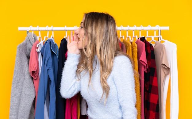 Jovem mulher em uma loja de roupas, gritando com a boca aberta
