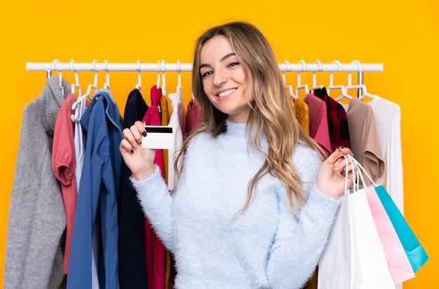 Jovem mulher em uma loja de roupas, segurando um cartão de crédito e com sacolas de compras