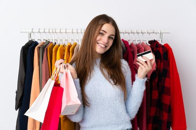 Jovem mulher em uma loja de roupas, segurando um cartão de crédito