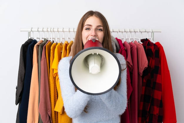 Jovem mulher em uma loja de roupas, segurando um megafone