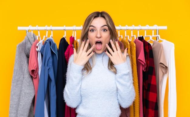 Jovem mulher em uma loja de roupas sobre parede amarela isolada com expressão facial de surpresa