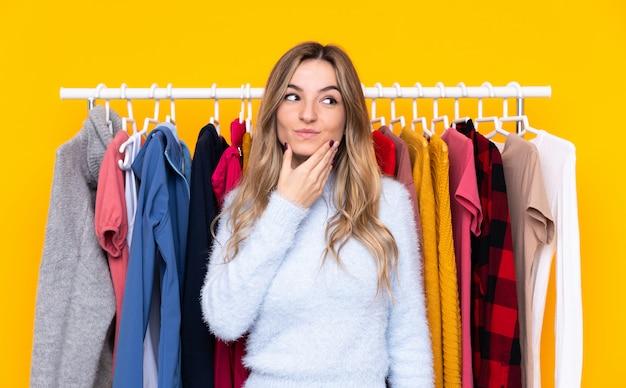 Jovem mulher em uma loja de roupas sobre parede amarela isolada, pensando uma idéia