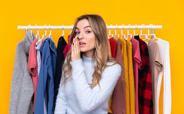 Jovem mulher em uma loja de roupas sobre parede amarela isolada sussurrando algo