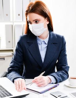 Jovem mulher em uma máscara protetora no local de trabalho.