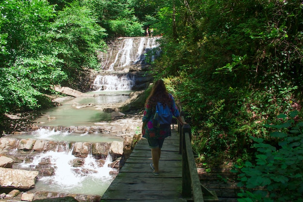 Jovem mulher em uma mochila de waterfallwith volta para a câmera