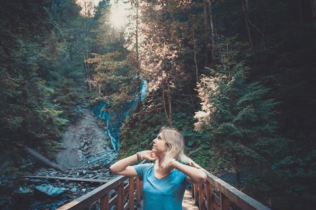 Jovem mulher em uma ponte na floresta, brilho do sol brilhar por trás das árvores. processamento de pastel