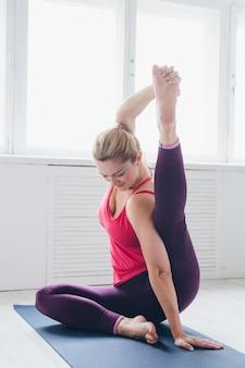 Jovem mulher em uma sala branca fazendo exercícios de ioga.