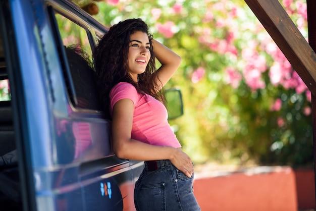 Jovem mulher em uma van de campista em um belo acampamento com flores cor de rosa