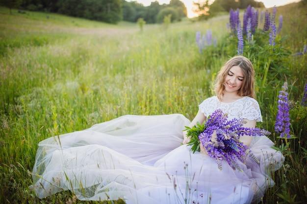 Jovem, mulher em vestido rico, senta-se com ramo de flores violetas no campo verde