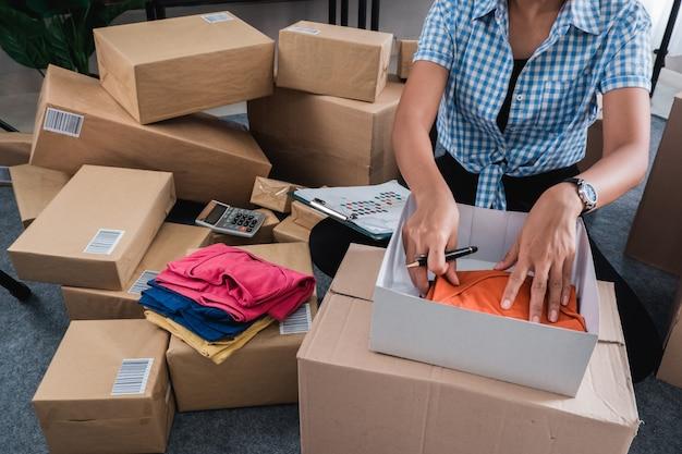 Jovem mulher embalagem de roupas, colocar nas caixas