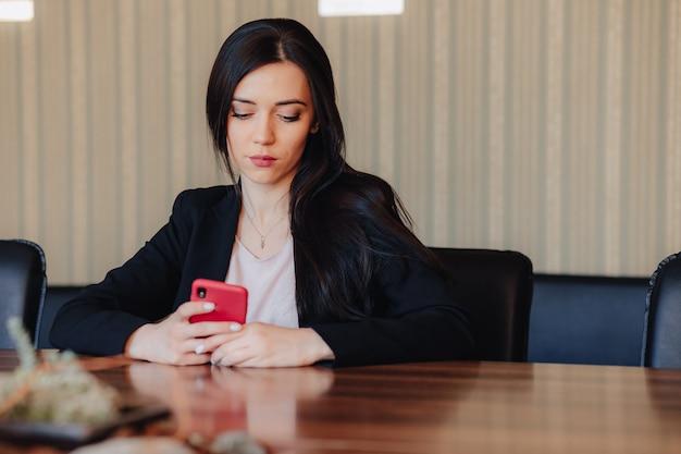 Jovem mulher emocional atraente em roupas de estilo empresarial, sentado na mesa com telefone