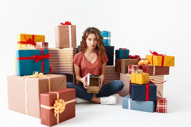 Jovem mulher encaracolada chateada, sentada no chão entre caixas de presente, mostrando uma que ela abriu está vazia