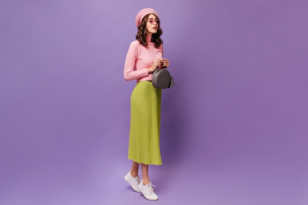Jovem mulher encaracolada com saia verde midi e boina rosa caminhando na parede roxa
