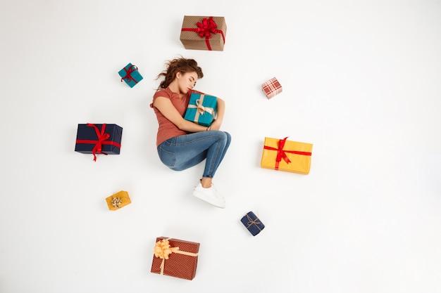 Jovem mulher encaracolada deitado entre caixas de presente