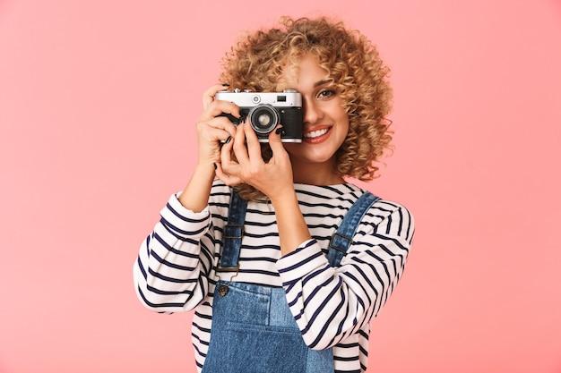Jovem mulher encaracolada dos anos 20 fazendo fotos na câmera retro em pé