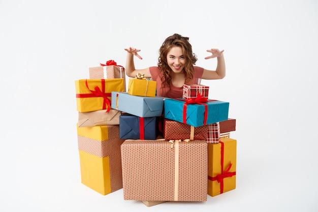 Jovem mulher encaracolada entre caixas de presente