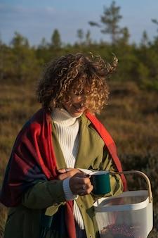 Jovem mulher encaracolada se aquecendo depois de colher cranberry no pântano segurando uma caneca de chá quente ou café sorrindo