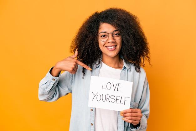 Jovem mulher encaracolada segurando um cartaz de amor a si mesmo apontando com a mão para um espaço de cópia de camisa, orgulhosa e confiante