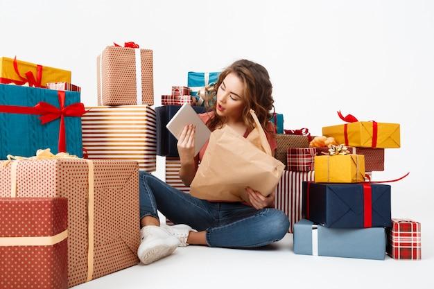 Jovem mulher encaracolada, sentada no chão entre caixas de presente, abrindo presentes