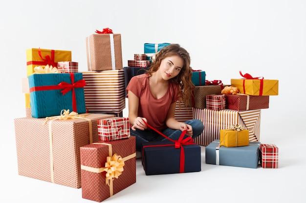 Jovem mulher encaracolada, sentada no chão entre caixas de presente, abrindo um deles