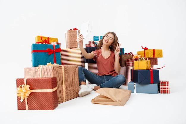 Jovem mulher encaracolada, sentada no chão entre caixas de presente, fazendo selfie com tablet