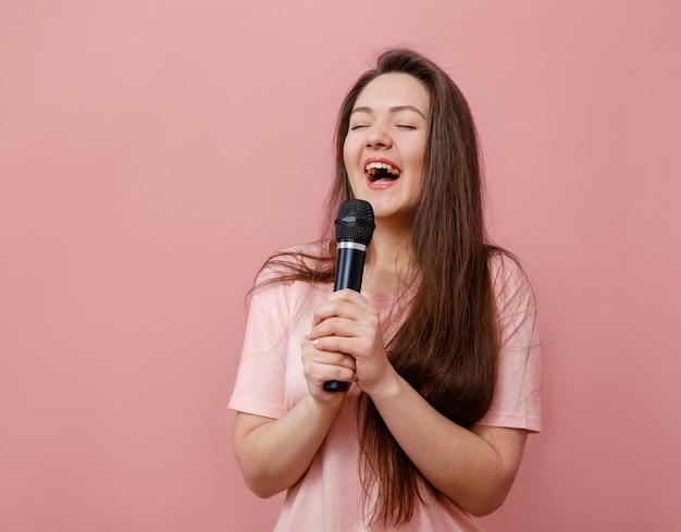 Jovem mulher engraçada com microfone na mão em fundo rosa