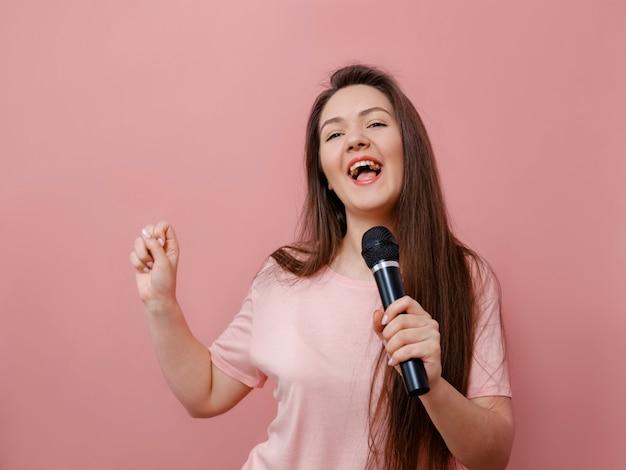 Jovem mulher engraçada com microfone na mão