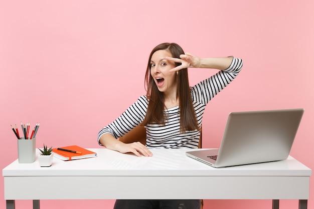 Jovem mulher engraçada e animada com a boca aberta mostrando o sinal da vitória, sente-se no trabalho na mesa branca com um laptop pc