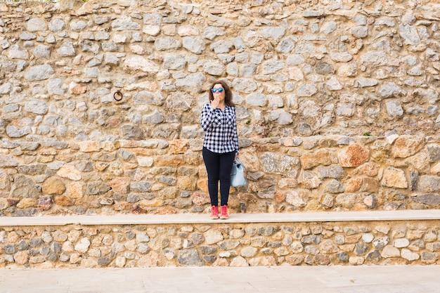 Jovem mulher engraçada e emocional com bolsa posando em meio urbano de pedra