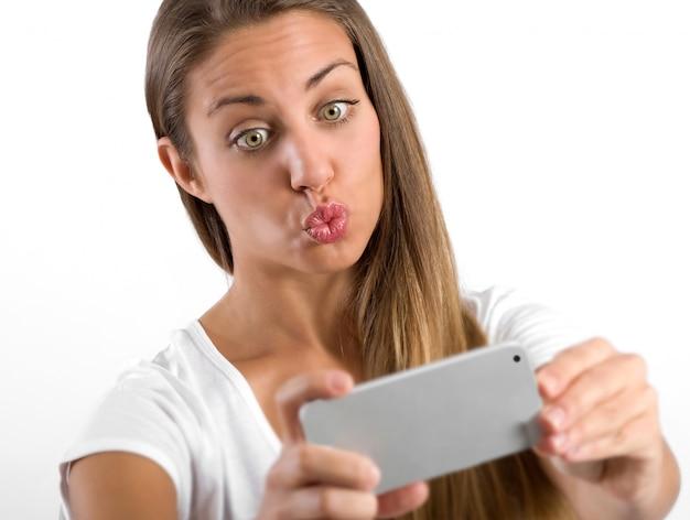 Jovem mulher enrugada para uma selfie franzindo os lábios como se estivesse pedindo um beijo