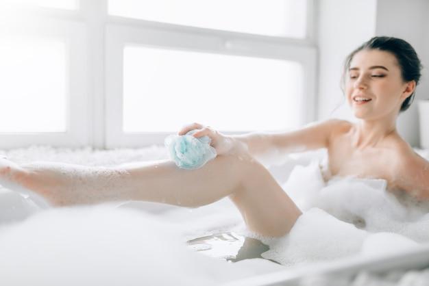 Jovem mulher ensaboa o corpo com uma esponja