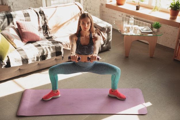 Jovem mulher ensinando em casa cursos on-line de fitness, estilo de vida aeróbio e esportivo durante a quarentena. ficar ativo enquanto isolado, bem-estar, conceito de movimento. exercícios com pesos, equilíbrio.