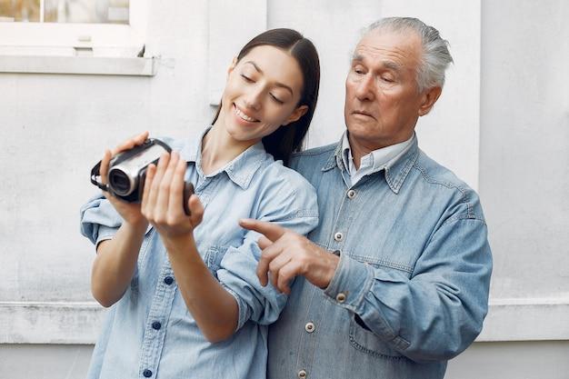 Jovem mulher ensinando seu avô como usar uma câmera