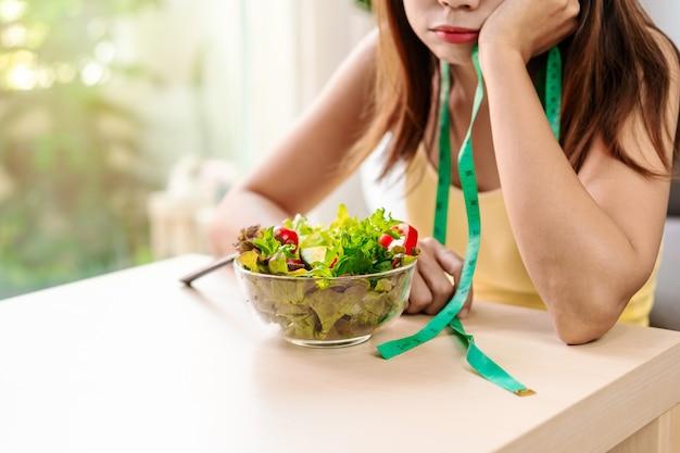 Jovem mulher entediante enquanto come vegetais frescos em casa