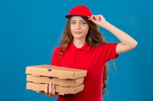 Jovem mulher entregadora descontente com cabelo encaracolado, vestindo uma camisa pólo vermelha e boné em pé com caixas de pizza saudando com o rosto infeliz sobre um fundo azul isolado