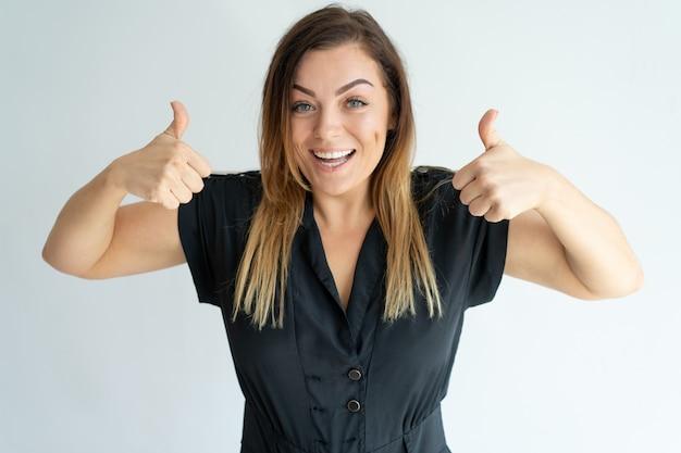 Jovem mulher entusiasmado positiva que mostra os polegares-acima e que tem o divertimento.